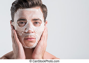 Serious guy is enjoying moisturizing procedure