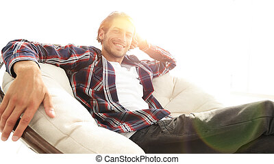 serious guy rests sitting in a large comfortable chair. side...