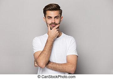 Serious guy touch chin look at camera thinking studio shot