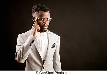 serious handsome businessman with black skin in glasses is...