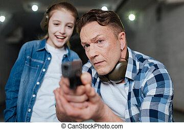 Serious handsome man holding using a handgun