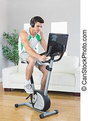 Serious handsome man training on exercise bike using laptop