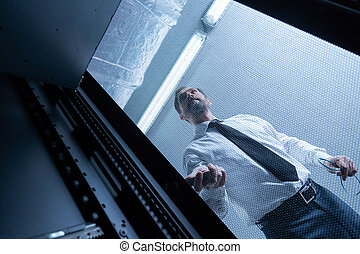 Serious handsome technician checking the network server