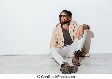 Serious hipster guy looking aside sitting isolated