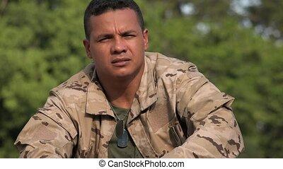 Serious Hispanic Male Soldier Talking  Wearing Camo
