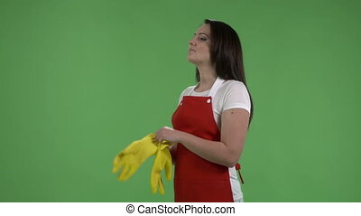 Serious housewife pulling rubber gloves ready for cleaning...