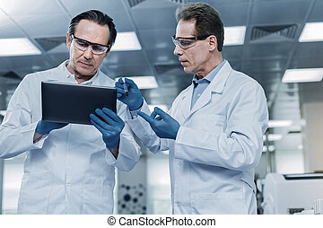 Serious intelligent man holding a tablet