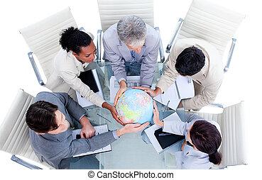 Serious international business team holding a terrestrial globe