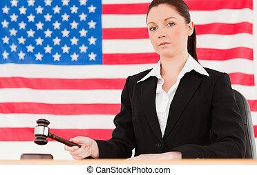 Serious judge knocking a gavel