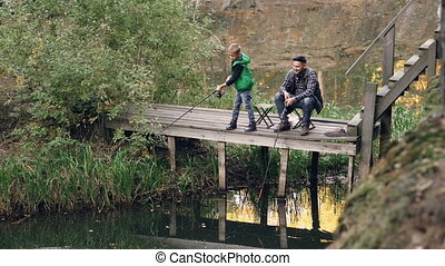 Serious kid is standing on wooden pier and fishing holding...