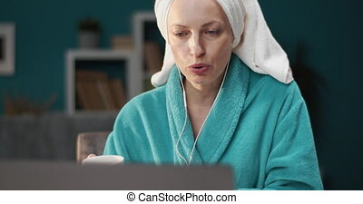 Serious lady in bathrobe and earphones having video call - ...
