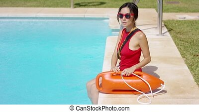 Serious lifeguard in red swimsuit and sunglasses sitting at side of pool holding rope connected to life buoy with handles