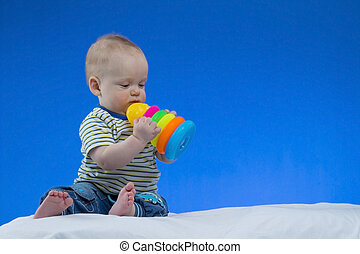 Serious little baby boy, sitting on the white blanket with a toy in hands , studio shot, isolated on blue background