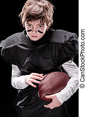 little boy american football player holding rugby ball and looking at camera