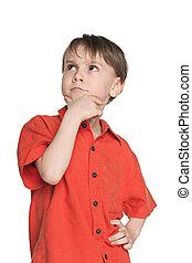 Serious little boy in a red shirt