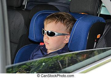 Serious little boy in car