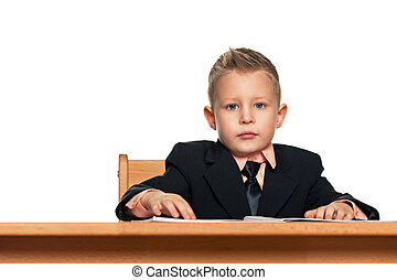 Serious little boy in suit at the desk
