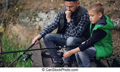 Serious little boy is catching fish with his father bearded...