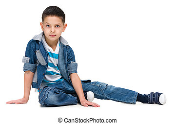 Serious little boy sits - A serious little boy sits on the ...