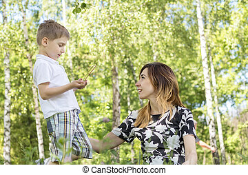 Serious little boy talking with his mother in the city park on a summer sunny day