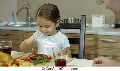 Serious Little girl having family dinner