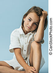 Serious little girl in a white thick romper suit sitting on the floor