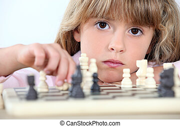 Serious little girl playing chess