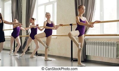 Serious little girls are learning sequence of ballet...