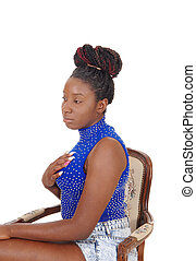 Serious looking African woman sitting in a chair