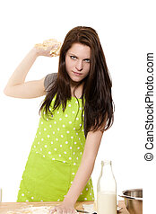 serious looking woman about to throwing dough in front of white background