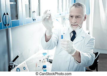 Serious male biologist standing in the lab