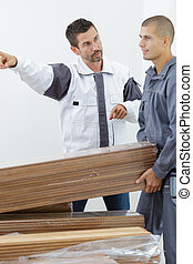 serious male carpenter showing something to coworker