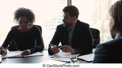 Serious male ceo consulting clients or team explaining ...