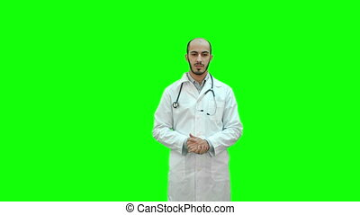 Serious male doctor talking to the camera on a Green Screen, Chroma Key.