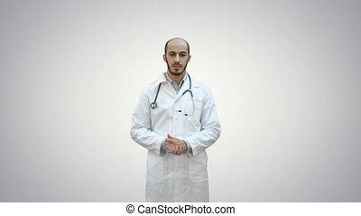 Serious male doctor talking to the camera on white background.