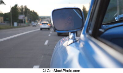 Serious male driver is reflected in left side mirror of the moving retro car. Young man driving a blue vintage auto on asphalt road. Background is defocused. Rear back view Close up Slow motion