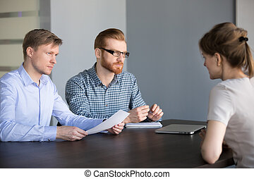 Serious male hr team listening female applicant at job interview