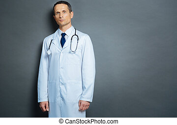 Serious male physician posing for camera over grey background