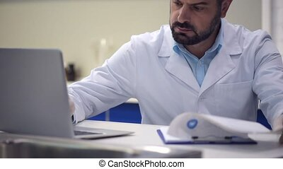 Serious male researcher typing in data while working on laptop