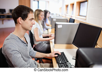 Serious male student working with a computer