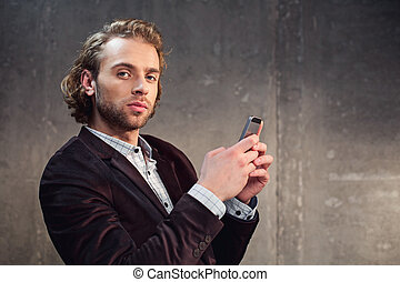 Serious male using modern mobile