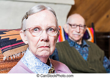Serious Man and Woman Indoors - Old couple seating in...