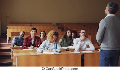 Serious man high school teacher is talking to students then young guy in glasses is raising hand and asking question. Education, lecture and college concept.