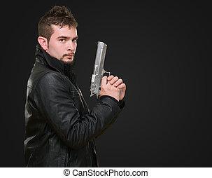 serious man holding a gun against a black background