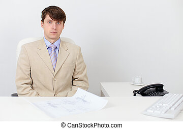 Serious man in a business suit at work in office