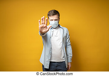 Serious man in a medical mask on his face makes a stop gesture with his hand, protecting against the virus. Health concept.