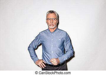 a335a4fefa25 Older man in blue denim shirt and glasses looking glum. An older man ...