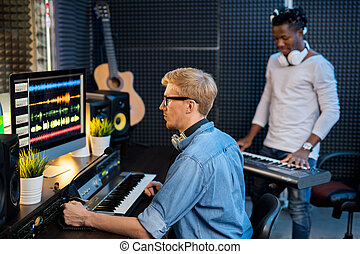 Serious man in denim shirt working with sound waveforms in ...