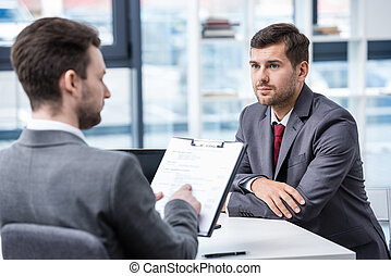 Serious man in formal wear looking at businessman with clipboard during job interview, business concept