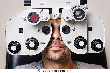 Serious man in phoropter with eye calibration